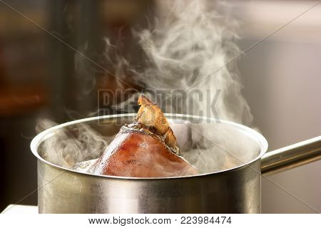 Evaporation from water with pork knuclke. Steam from the saucepan with meat.