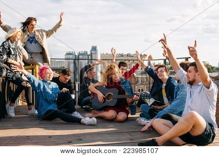 Carefree exchange students singing together on a rooftop their hands in the air. Bonding, friendship youth happiness