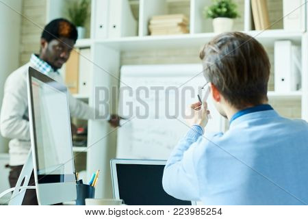 Portrait of two people, one of them African, brainstorming over business project while working in modern office, copy space