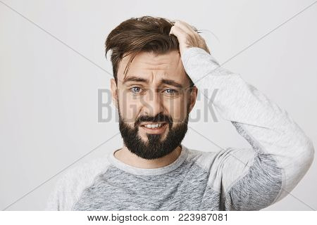 Miserable and gloomy guy with messy hair, frowning and looking unsatisfied while scratching head, standing over gray background. Something heavy fell on his head, man feels pain.