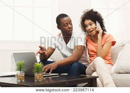 Young couple web surfing on laptop sitting on sofa at home, woman talking on phone, relaxing. Freelance, remote work and online shopping concept, copy space