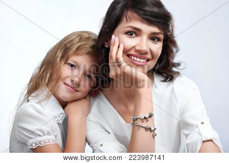 Studio portrait of wonderful family couple: beatiful mother and her little nice daughter. They are very happy with pretty smiles. They wear white t-shirts. Close-up was made on a studio background.