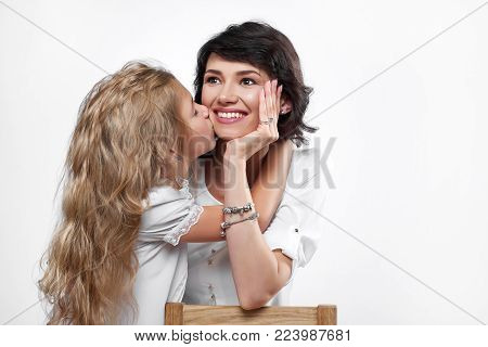 Photo of a happy mother with a daugher, who kisses her. She is very beatiful and smiling. A kid hugs and kisses her very sincerely. They wear white t-shirts. Portrait was made on a studio background.