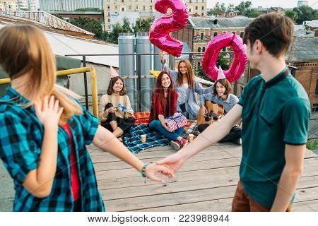 20th birthday surprise. Friends waiting for a girl with balloons. Celebration, congratulation