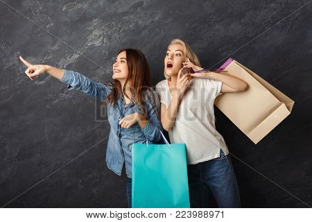 Happy casual girlfriends with shopping bags. Two excited shopaholics looking for sales and sharing info by smartphone at black sudio background with copy space