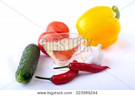 Assorted vegetables, fresh bell pepper, tomato, chilli pepper, cucumber, olive oil, garlic and lettuce isolated on white background. Selective focus