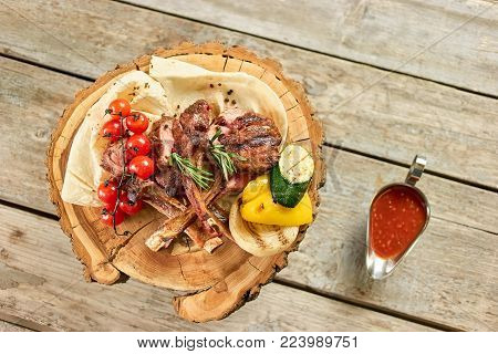 Top view on dish with roasted lamb ribs with tomatoes and sauce. Roasted lamb ribs with tomatoes on wooden plate and red sauce in metal pot, top view.