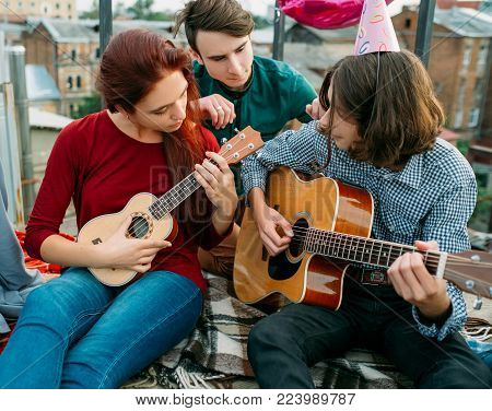 Musical artistic duet. Guitar and ukulele string instruments play. Musician lifestyle. Teenagers leisure
