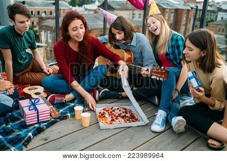 Pizza delivery to the rooftop. Unconventional birthday food. Youth eating preferences. Tasty and delicious food. Happy hungry teenagers