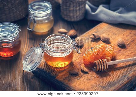 Honey in glass jars, nuts almonds and honey dipper on a wooden table. Toned