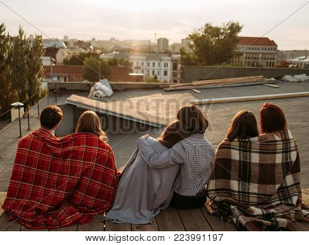 Teen relationship and dating. Back view of diverse couples in love sitting together on a rooftop and enjoying sunset poster