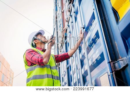 Asian foreman control loading Containers box checking containers for Logistic Import Export in dock