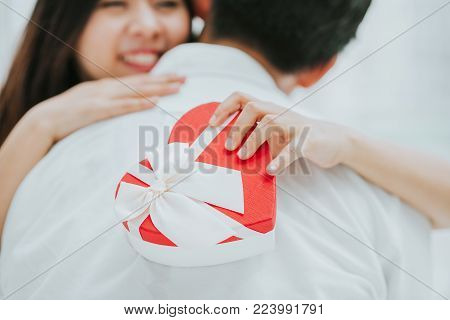 Happy beautiful young Asian woman embracing her boyfriend after receive valentine gift. focus on the gift box