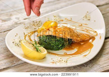 Cooker adding garnish to the dish, closeup. Hand adding garnish to the salmon with sauce dish, closeup.