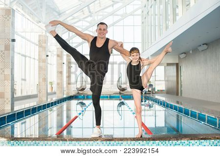 Group portrait of pretty little girl and her middle-aged swimming coach standing on edge of pool with one leg raised and looking at camera with toothy smiles.