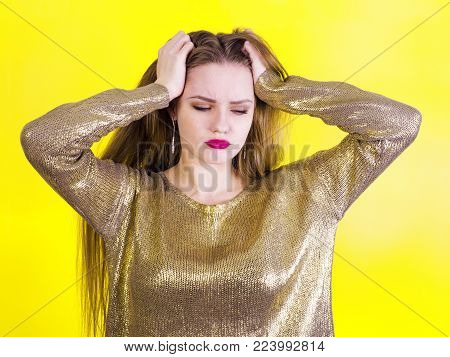 Frustrated young and beautiful woman looks upset, depressed and holds her head hand on a yellow background