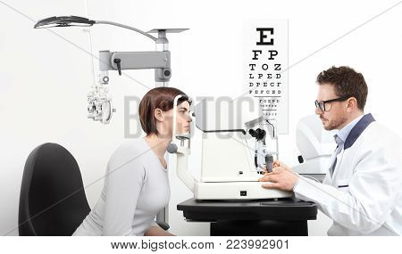 optometrist examining eyesight  patient in optician office on white background