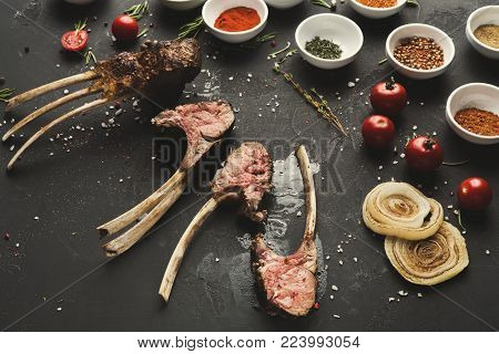 Grilled rack of Lamb. Bbq meat with spices assortment on black table, restaurant food