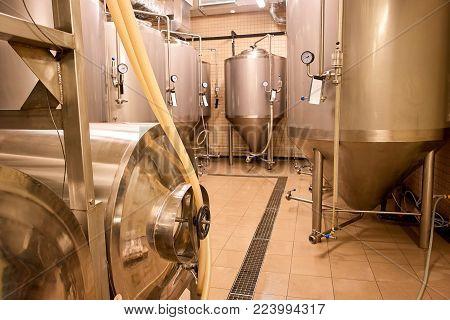 Steel brewery kettles indoor. Beer plant with brewing kettles.
