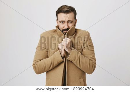 Portrait of gloomy bearded man who is freezing, holding tight his coat to warm up, standing over gray background. Sometimes weather act unpredictably. Guy regrets not to wear warmer clothes. Copy space