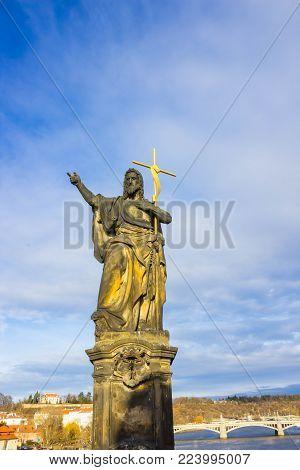 Prague, Czech Republic - December 31, 2017: The gothic sculpture of the John the Baptist on the Charles bridge. Prague, medieval art, statue of Saint on the bridge of King Charles.