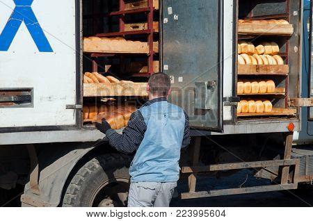 Murmansk, Russia - August 28, 2012: The worker unloads fresh bread from the truck