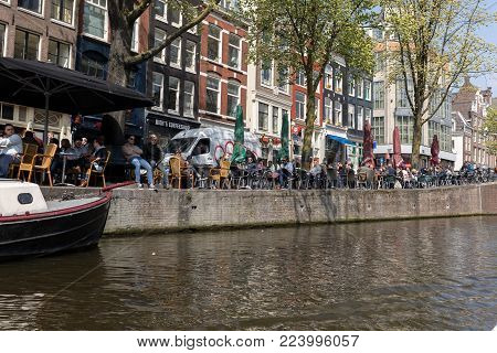 Amsterdam, Netherlands - April 20, 2017: People sitting at sidewalk cafe by canal with facades of traditional houses in background. Amsterdam, Netherlands