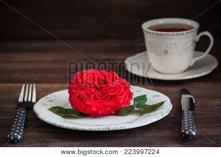 Romantic dinner setting with fresh red garden rose. Valentine or Wedding postcard concept. Toned.