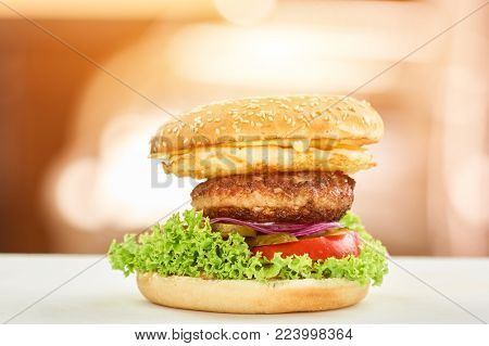 Big hamburger with many layers. Closeup hamburger with cheese, chop, burger patty, onion, pickled cucumbers, tomato slice and lettuce.