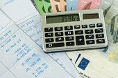 Financial tax or debt calculation for office salary man  concept as calculator on pile of euro banknotes with numbers on carbon salary slips. poster