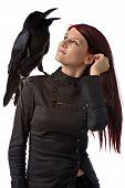 young woman looking like a witch in black clothes with big raven on her shoulder isolated on white poster
