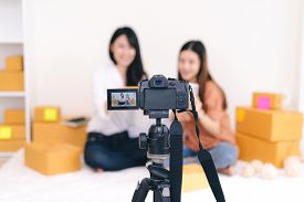 Teamwork asian women freelancer and blogger review product working sme business at home office with parcel box for delivery online to customer by talking camera live recording video on social network