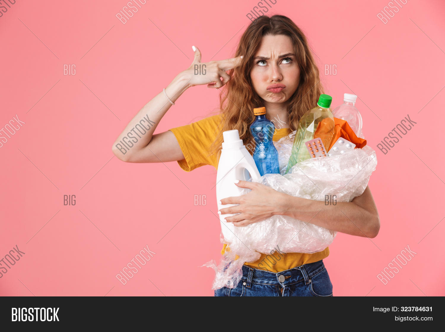 Photo of displeased caucasian woman in basic t-shirt holding plastic waste and showing gun gesture isolated over pink background