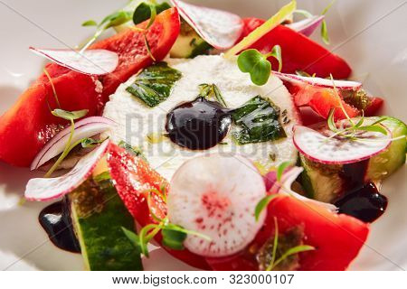 Exquisite serving salad of fresh vegetables, ricotta cheese and fragrant herbs on white restaurant plate isolated. High cuisine restaurent dish with delicious greek village salat closeup