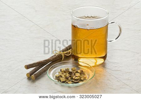Glass of licorice tea and pieces of roots in front of the cup