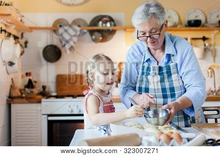 Family Is Cooking In Cozy Kitchen At Home. Grandmother And Funny Kid Are Making Italian Meal. Senior