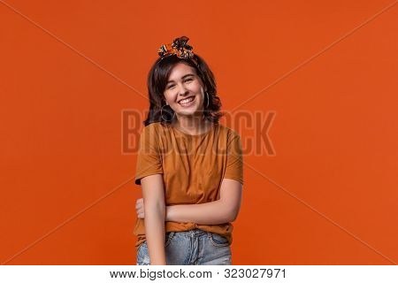 Smiling Brunette Woman In An Orange T-shirt And Beautiful Headband Looking At The Camera Standing Is
