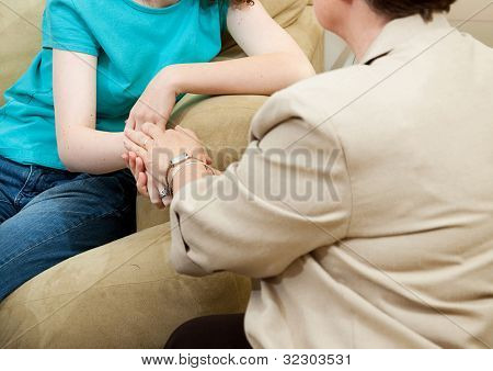 Depressed girl gets counseling and comfort from a caring therapist.