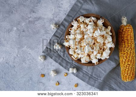 Traditional Popcorn In A Wooden Bowl And Corncobs On The Table.