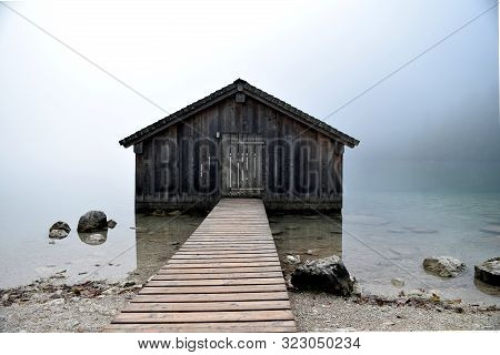 Mystical Landscape Of A Hut On The Shore Of A Lake In The Fog.