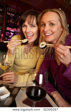 Two Women Enjoying Sushi In Restaurant