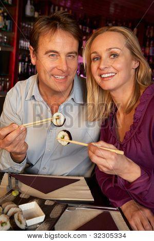 Couple Enjoying Sushi In Restaurant