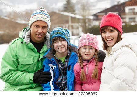 Portrait Of Family Wearing Winter Clothes In Snowy Landscape