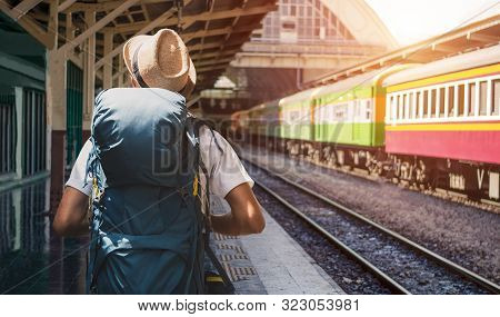 Young Asian Man Traveler With Backpack In The Railway, Backpack And Hat At The Train Station With A