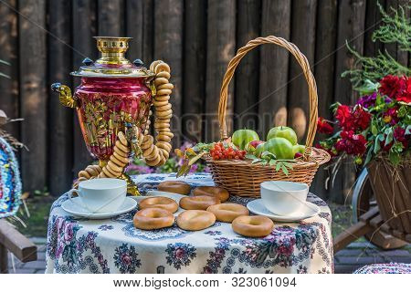 Round Table With A Samovar, Cups, Bagels And A Basket Of Apples
