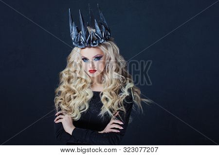 Chic Gothic Queen From A Dark Fairy Tale. Young Blonde Woman In Black With Steel Crown On Her Head.