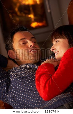 Middle Aged Couple Chatting On Sofa By Cosy Log Fire
