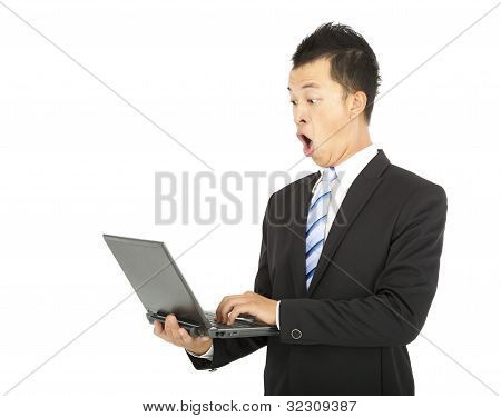 surprised business man watching the laptop computer
