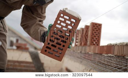 Worker Puts A Brick Wall. Bricklayer Working In Construction Site Of A Brick Wall. Bricklayer Puttin