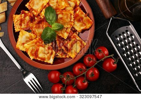 Ravioli With Tomato Sauce Garnished With Parmesan Cheese And Basil On Rustic Table